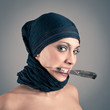 Veiled woman holding a knife against dark background.