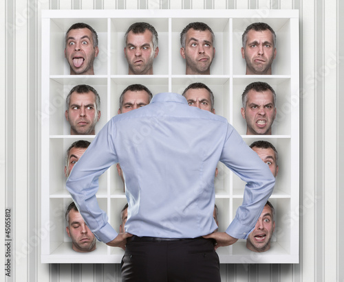 Young man choosing which face expression to wear