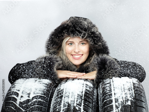 Pretty woman with winter coat behind snowy winter tyres