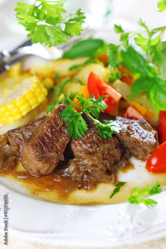 Beef stew with vegetables and salad of fresh tomato.