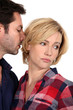 Husband kissing unhappy wife