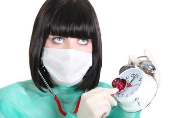 Female doctor using stethoscope on alarm clock