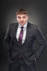 A young man in a suit with a perturbed look on his face, looking