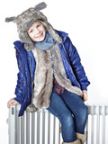 Cute girl with pelt cap is sitting on a radiator to keep warm poster
