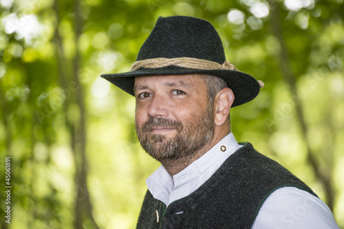 Man with Bavarian traditional black hat iin forest
