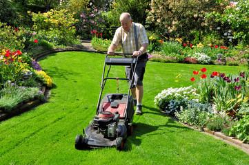 Senior mäht den Rasen im Garten