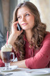 A woman in restaurant is talking to mobile phone