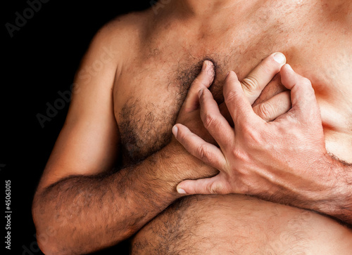 Shirtless man suffering a heart attack isolated on black