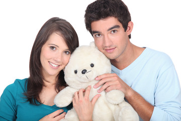 Young couple holding stuffed toy