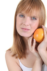 bust shot of red-haired girl posing with orange