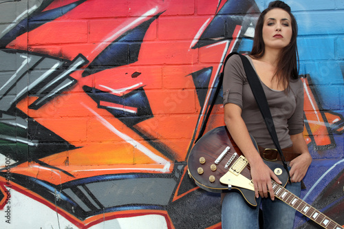 Woman with guitar in front of graffiti