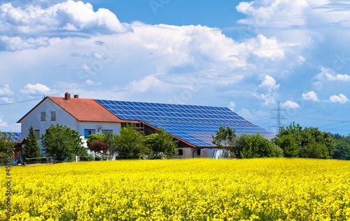 Bauernhof mit Solarzellen im Rapsfeld