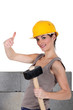 craftswoman holding a hammer and making a thumbs up sign