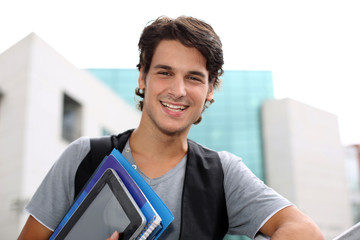 Cheerful student standing outside college building