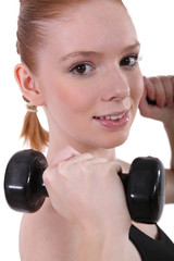 Girl lifting dumbbells, studio shot