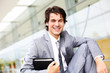 Smiling young businessman sitting outside building