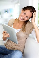 Young woman using electronic tablet sitting on sofa
