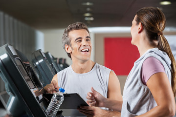 Happy Instructor Looking At Female Client Exercising On Treadmil