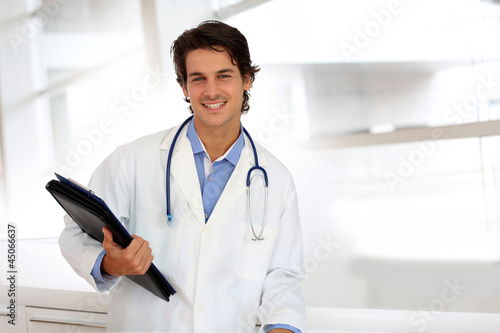 Cheerful student in medicine standing in hospital hallway