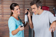 Instructor Assisting Man In Getting Down From Exercise Machine