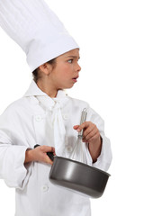 little girl dressed as a chef holding a whisk