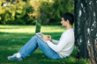 Young man sitting near the tree stem and using laptop