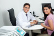 Happy Dentist And Patient At Office Desk