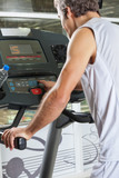 Man Pressing Program Button on Treadmill