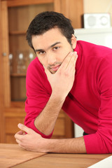 young dark-haired guy in kitchen wearing raspberry red jumper