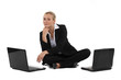 Blond businesswoman sat on the floor with two laptops