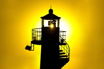 Lighthouse silhouetteat yellow sunset
