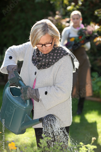 Senior woman watering flowers in her garden