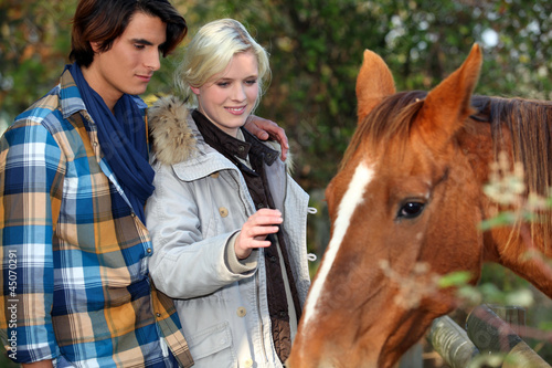 Young couple petting horse