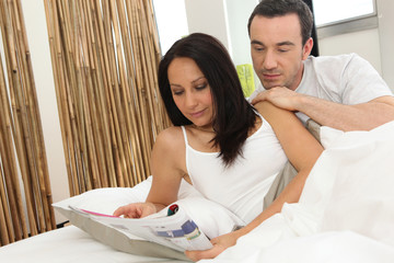 Couple in bed looking at a magazine