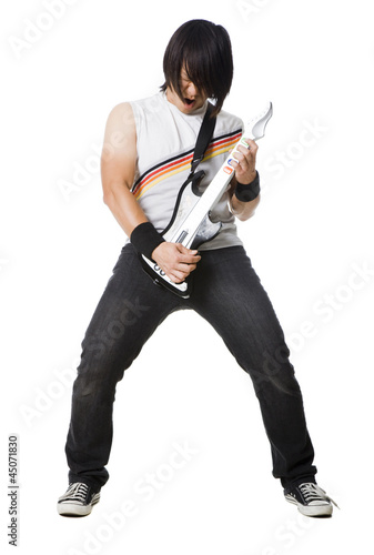 """Young man playing guitar video game and screaming, studio shot"""
