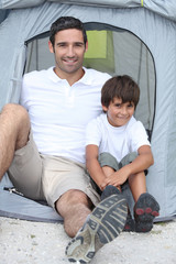 Father and son in front of tent