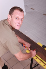 Man measuring laminate flooring
