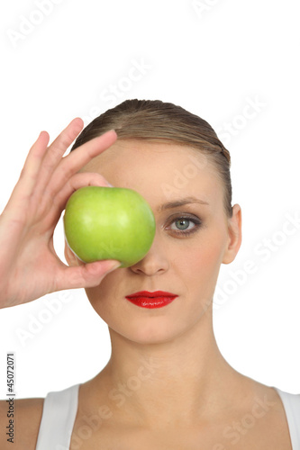 Woman holding green apple over her eye