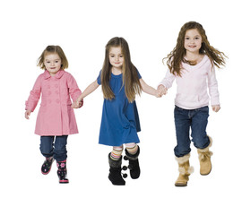 Studio portrait of three girls (2-7) holding hands