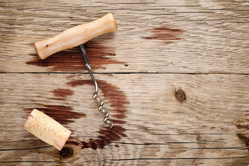 Corkscrew, cork and wine stains on wooden background