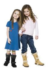 Studio portrait of two girls (4-7) arm in arm