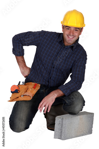 craftsman posing next to a stone block
