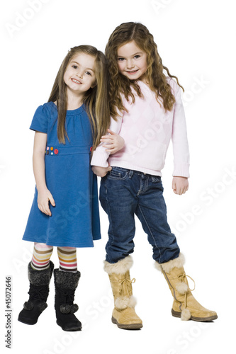 Studio portrait of two girls (4-7) arm in arm
