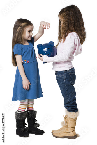 """Two girls (4-7) putting money in piggy bank, studio shot"""