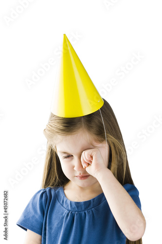 Studio portrait of upset girl (4-5) wearing party hat