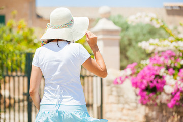 Back view of cute young woman in summer hat