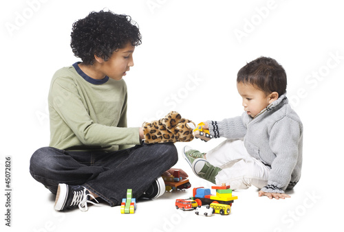 """Brothers (18-23 months) (8-9) playing with toys, against white background"""