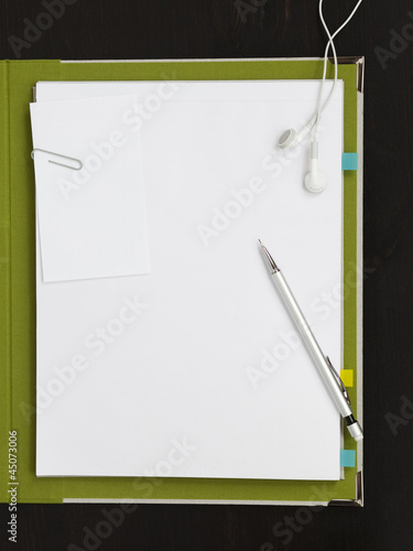 """Earphones, pencil and paper clip on blank paper with file"""