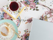 Food and drink with glasses and laptop on floral tablecloth