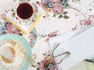 """Food and drink with glasses and paper, on floral tablecloth"""